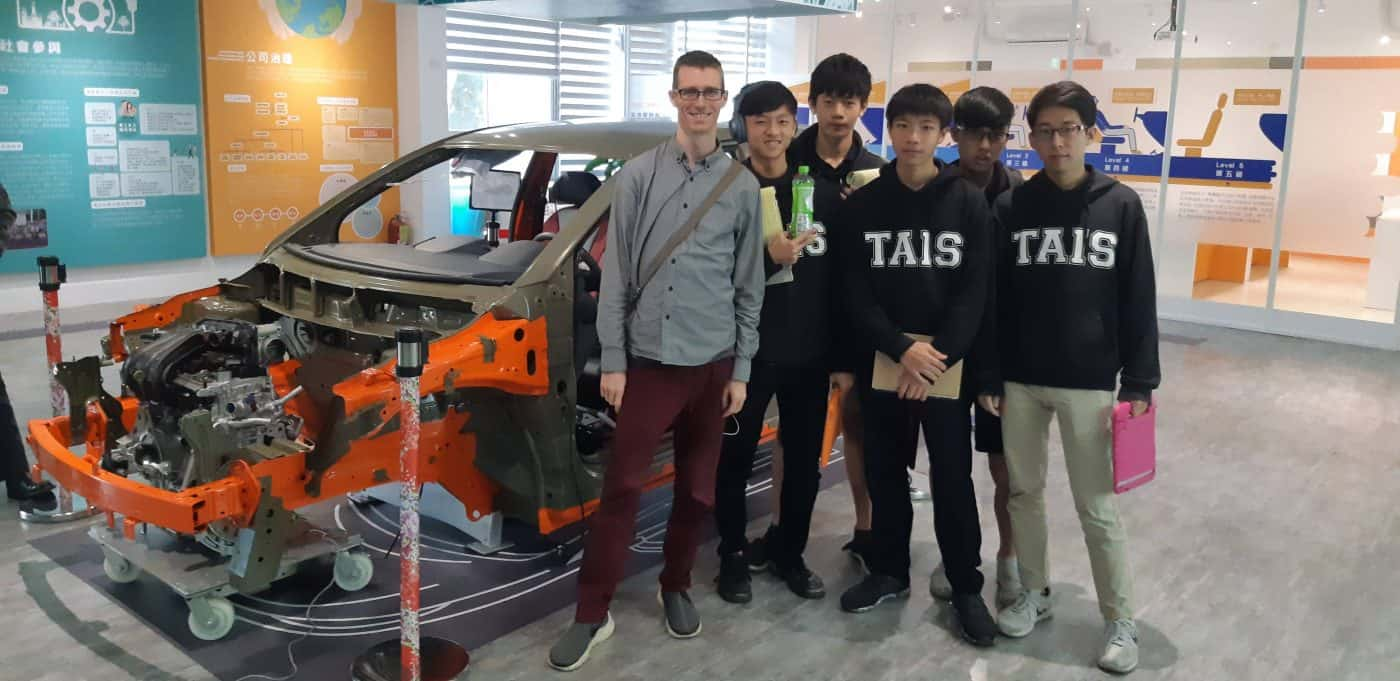 students stand in front of cutaway car