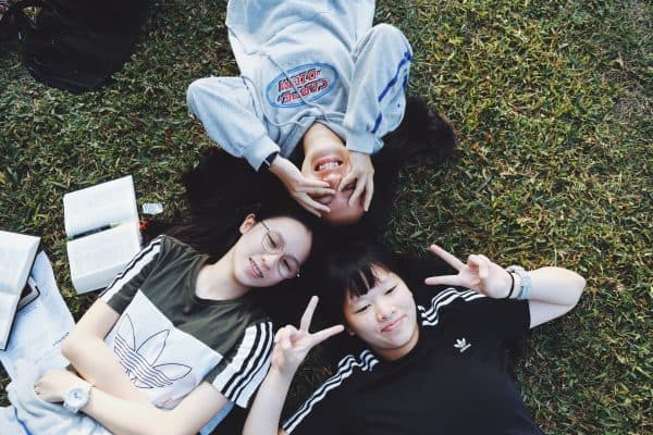 girls laying on grass together