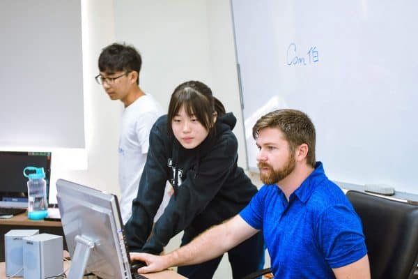 teacher and student look at computer screen
